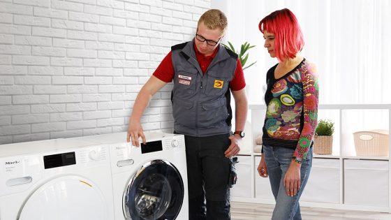 Mitarbeiter zeigt Kundin eine Waschmaschine